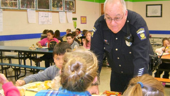 Mansfield Police Officer Jack Shay talks with students in the cafeteria at Malabar Intermediate School.