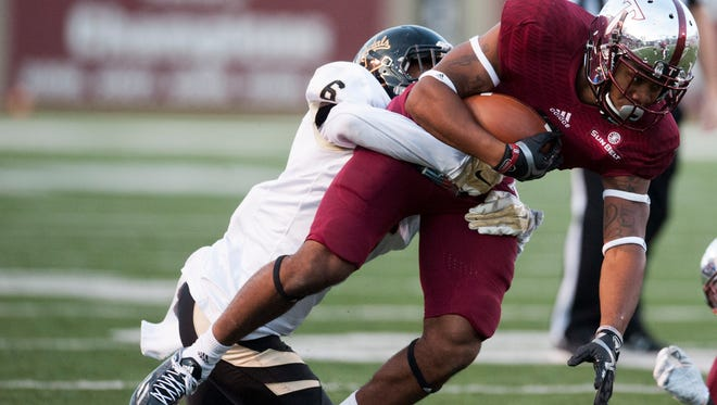 Troy's Emanuel Thompson is stopped by Idaho's Kendrick Trotter (6) at Veterans Memorial Stadium in Troy, Ala. on Saturday October 17, 2015. (Mickey Welsh / Montgomery Advertiser)
