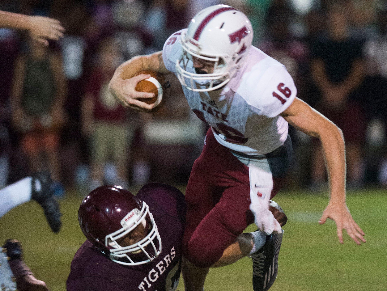 Pensacola High School linebacker Isaiah Brown, (No. 26) trips up Tate High School quarterback Jake Henry, (No. 16) during Friday night's preseason opener.