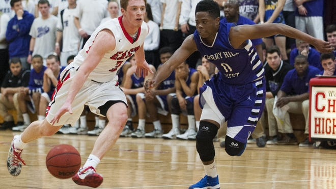Jake Silpe of Cherry Hill East looks to go past Elijah Bey of rival Cherry Hill West during a Group 4 playoff game.
