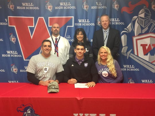 Wall's Eddie Scott is surrounded by his parents, coach and school administrators on Signing Day 2018 .