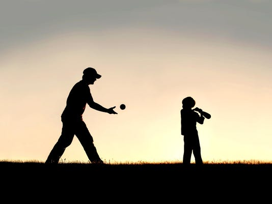 Silhouette of Father and Young Child Playing Baseball OUtside