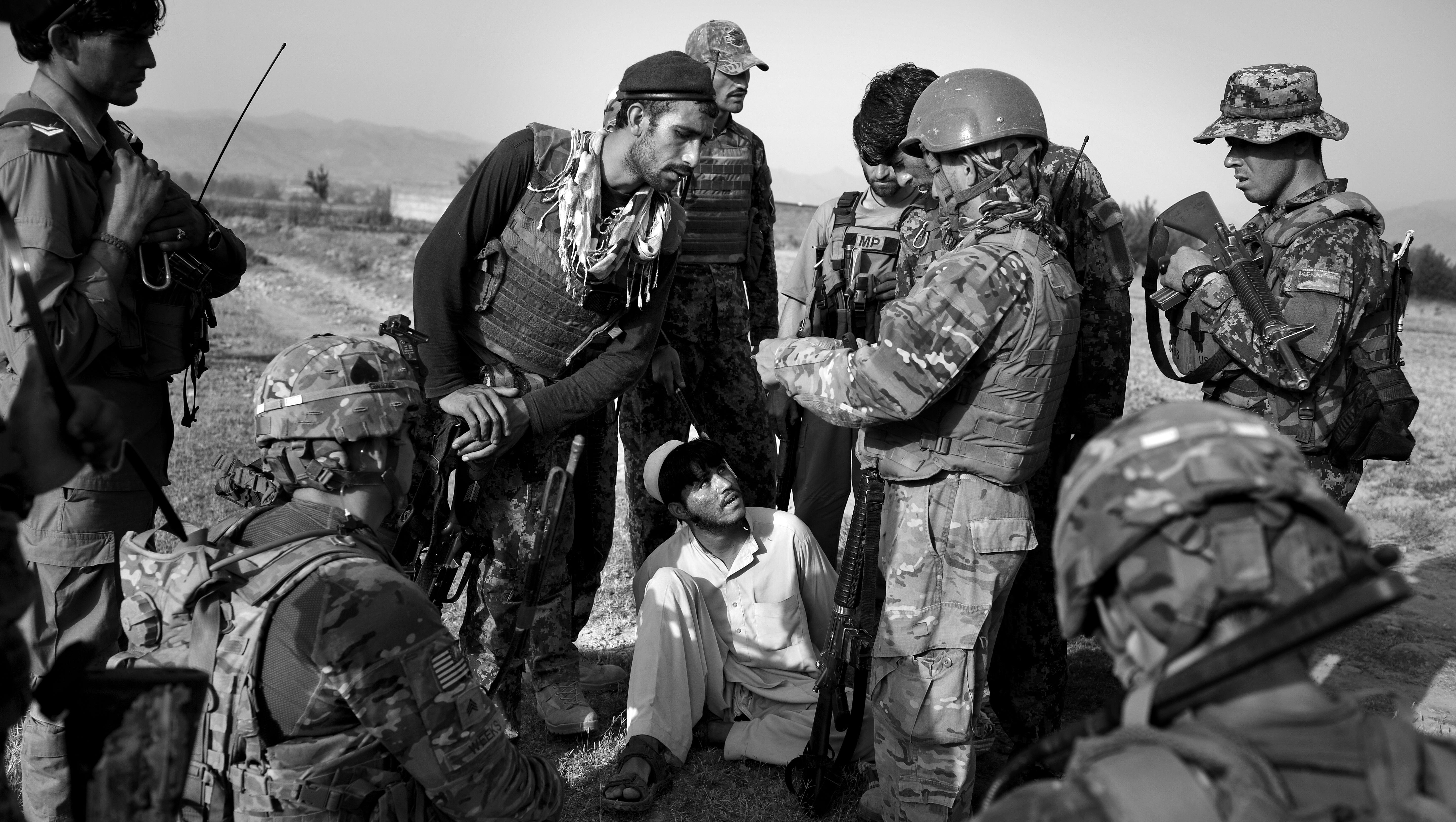 Afghan National Army soldiers and U.S. soldiers from 2nd Platoon Fox Co. of 2-506th Infantry Battalion of the 4th Brigade of the 101st Airborne Division interrogate Mulik, center, a young Afghan they suspect of insurgent ties after they found two IEDs nearby in Khost province.