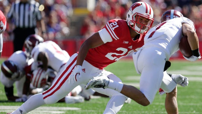 Wisconsin's Arrington Farrar stops Troy wide receiver Teddy Ruben for a short gain during their game in September 2015.