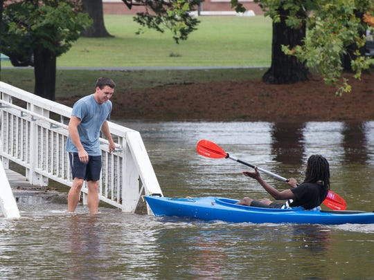 Two men on kayaks dock at the bridge in Salisbury City