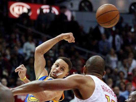 Golden State Warriors guard Stephen Curry (30) passes as Atlanta Hawks center Al Horford (15) defends in the second half of an NBA basketball game Monday, Feb. 22, 2016, in Atlanta. Golden State won 102-92. (AP Photo/John Bazemore)
