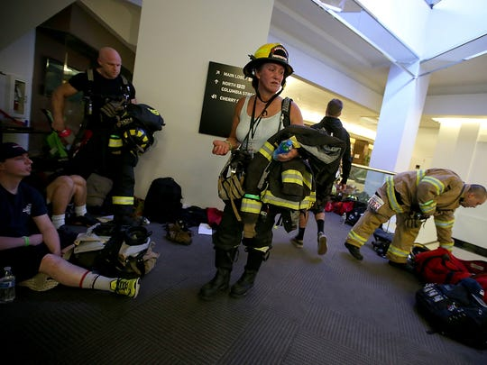 Poulsbo's Jaunitta Lang makes her way through the Columbia Center after climbing 69 floors in full bunker gear to the observation deck as part of the Scott Firefighter Stairclimb in downtown Seattle on Sunday, March 12, 2017.