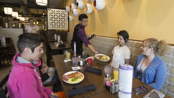 Andree Meignein, left, Jasmine Myles, far right, and Mandy Rades, right, are served breakfast on the opening day of Urban Egg this past May.