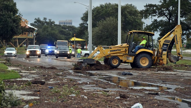 Biloxi public works employees clear debris from U.S. 90 in Biloxi Sunday, Oct. 8, 2017, after Hurricane Nate made landfall on the Gulf Coast.