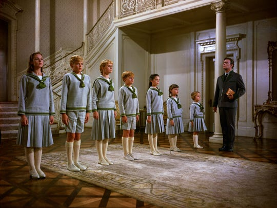 """Captain Von Trapp (Christopher Plummer) keeps his children in line in 1965's """"The Sound of Music."""" The youngsters, from left, are played by Charmian Carr, Nicholas Hammond, Heather Menzies, Duane Chase, Angela Cartwright, Debbie Turner and Kym Karath."""