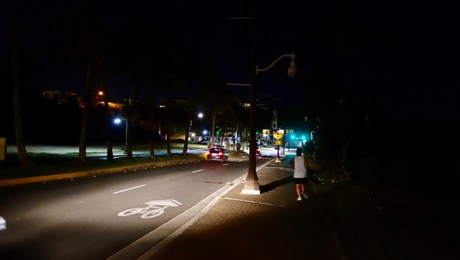 A jogger navigates the dimly lit Tumon streets at night. Broken street lights raised safety concerns in the popular tourism district.
