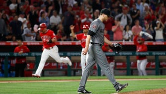 Arizona Diamondbacks starting pitcher Matt Koch walks back to the mound as Los Angeles Angels' Kole Calhoun, background left, runs the bases after hitting a home run during the sixth inning of a baseball game Tuesday, June 19, 2018, in Anaheim, Calif.