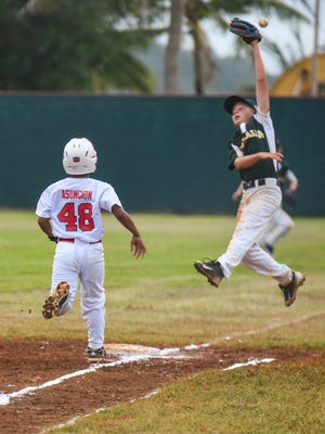 Guam's pitcher Elijah Asuncion (48) is safe at first after a throwing error during the U12 Oceania Baseball Championship Tournament against Guam at the Guerrero Stadium in Hagåtña on Thursday, Jan. 12, 2017.