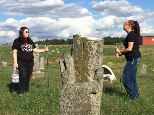 Brecca Mefford, left, and Sarah Vittur discuss their work with the Henderson County KY Cemetery Research Group while working at the Bethel Baptist Church cemetery at Hebbardsville. The gravestone shaped like a sawed-off tree in the foreground represents a life cut short.