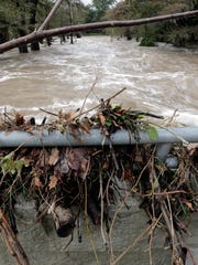 A swollen Guadalupe River sweeps past a debris covered