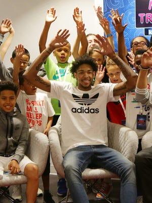 Former Duke University basketball player Brandon Ingram poses for a photo with children during the Kids Footlocker Media Day leading up to the NBA draft Thursday.