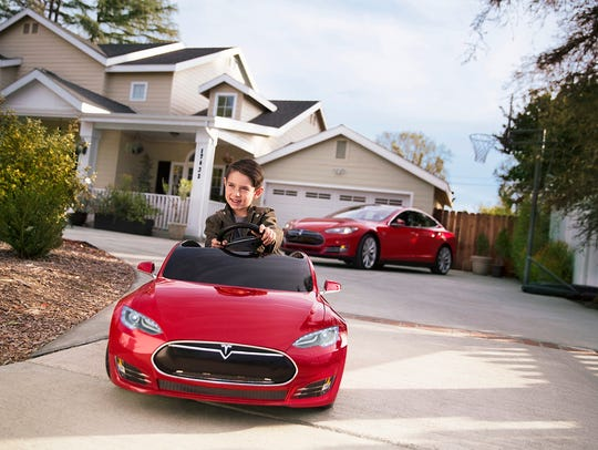 A boy drives a customized red Tesla Model S for kids