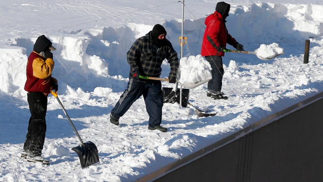 Workers clear snow from a roof in Boston, Monday, Feb. 16, 2015. New England remained bitterly cold Monday after the region's fourth winter storm in a month blew through.
