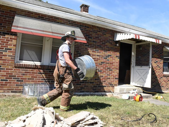 Firemen do salvage and cleanup at a house fire at 59