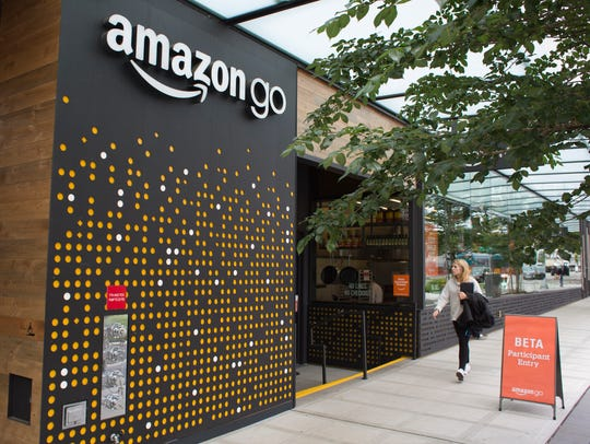 A woman walks past the Amazon Go grocery store at the
