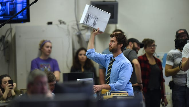 """Actor Ryan Churchill, who plays Zagger, tosses a package while filming a scene for """"The Sixty Yard Line"""" in the Green Bay Press-Gazette newsroom on Wednesday. The cast and crew will wrap up local filming on the Packers-themed romantic comedy on Tuesday."""