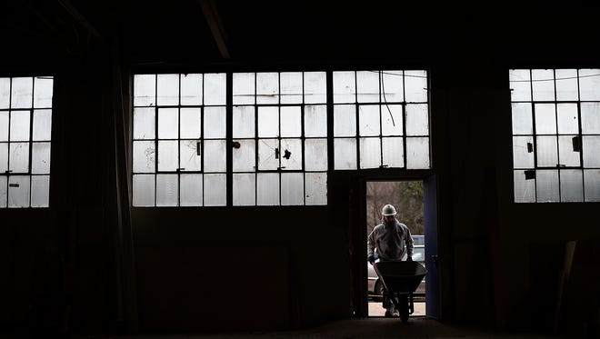Original steel windows from the 1920s surround a  construction worker from Immel Construction working on the renovation and restoration to Pete's Garage, 142 N. Broadway, in downtown Green Bay. The windows are being restored.
