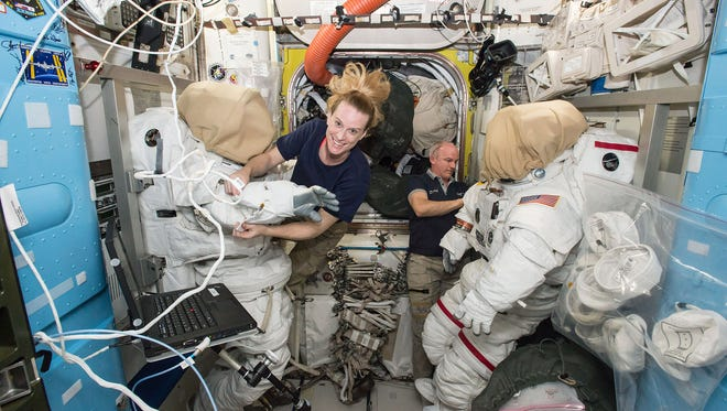 Expedition 48 crew members Kate Rubins and Jeff Williams of NASA outfit spacesuits inside of the Quest airlock aboard the International Space Station. Rubins and Williams plan to conduct a spacewalk on Friday, Aug. 19, 2016, to install a new docking port that will enable the future arrival of U.S. commercial crew spacecraft.
