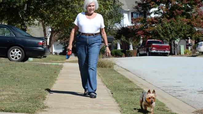 Janet Craig walks her dog Lucy around her Simpsonville neighborhood on Wednesday. Craig underwent a new procedure to lose weight that is an alternative to surgery.