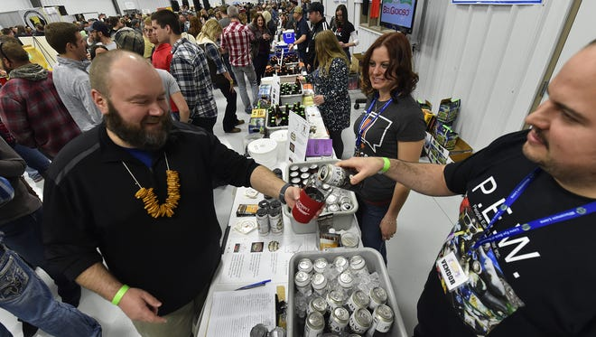 Corey Weinkoetz of Milwaukee-based craft brewery MobCraft Beer pours a sample of its Pivot Ale, a black ale, for Bill Gruhlke of Luxemburg at last year's Roar Off the Shore Brewfest,