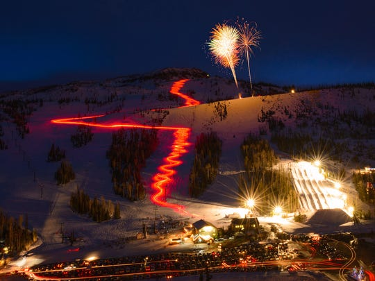 Fireworks explode in the air over Brian Head as the glow from the torch run streaks down the mountain on a past New Year's Eve in this image provided by Brian Head Resort.