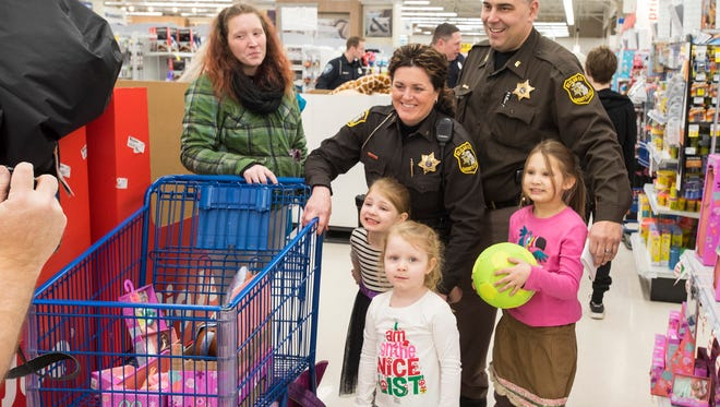 St. Clair County deputies Damon and Keri Duva stop for a photo with sisters McKenzie Groce, 8, Rosalee Groce, 6, and Jaklyn Groce, 4, at Christmas With A Cop, held Tuesday night at Meijer in Fort Gratiot.