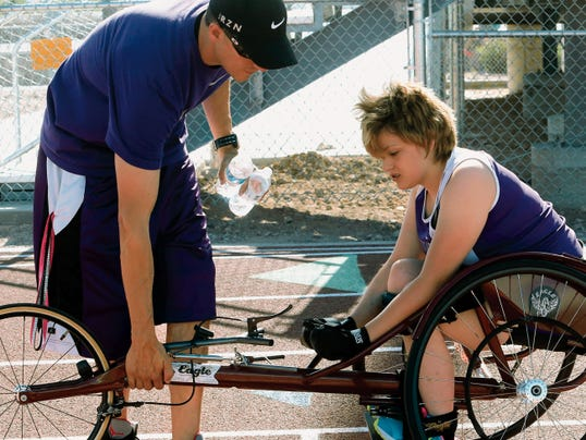 Emily Kirby gets help from assistant track coach Raul Nava in making an adjustment on her racing tricycle on the track on Monday at Franklin High School.