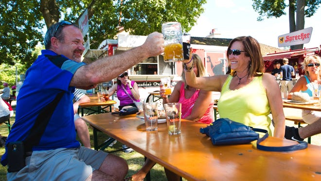 Roger Romens and Cindy Becker raise their glasses at the Traveling Beer Garden at the Brown Deer Park Golf Clubhouse in this 2015 photo.