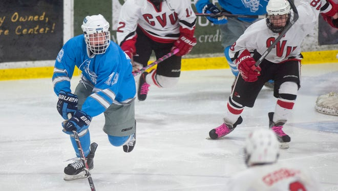 South Burlington's Michael Flaherty, left, skates out of the defensive zone with the puck during Wednesday's game against Champlain Valley.