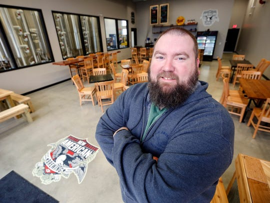 David Bryan, owner of New American Brewing stands for
