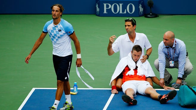 Jack Sock receives assistance from trainer Hugo Gravil for heat exhaustion as Ruben Bemelmans walks away during their match at the US Open at the USTA Billie Jean King National Tennis Center on Sept. 3, 2015.