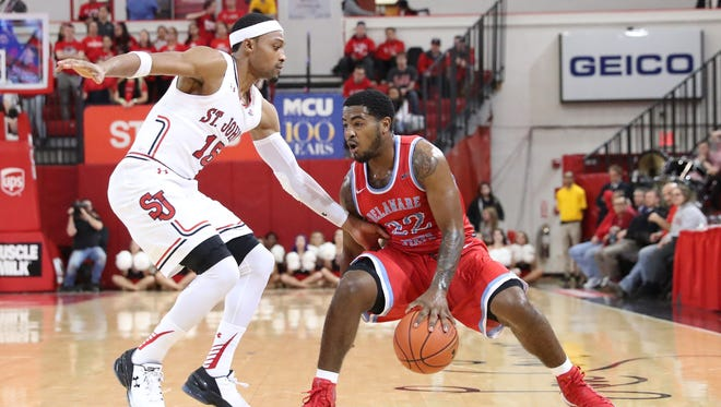 Delaware State guard Devin Morgan (22) works the ball as St. John's Red Storm guard Marcus LoVett (15) defends during the first half at Carnesecca Arena.