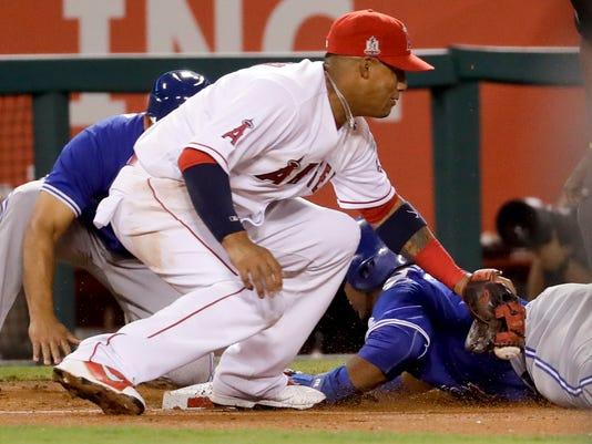 Toronto Blue Jays' Edwin Encarnacion, right, is safe at third under the tag by Los Angeles Angels third baseman Yunel Escobar on a single by Jose Bautista during the fourth inning of a baseball game in Anaheim, Calif., Thursday, Sept. 15, 2016. (AP Photo/Chris Carlson)
