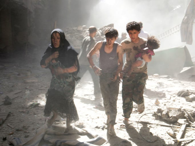 People in Aleppo flee the scene after Syrian government aircraft staged a barrel-bomb attack on June 26.