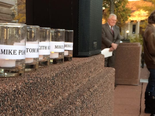 Candles bearing the names of the six men convicted in the 1992 murder of Thomas Monfils sat on a ledge outside the Brown County Courthouse in Green Bay as supporters rallied on the men's behalf in 2014.