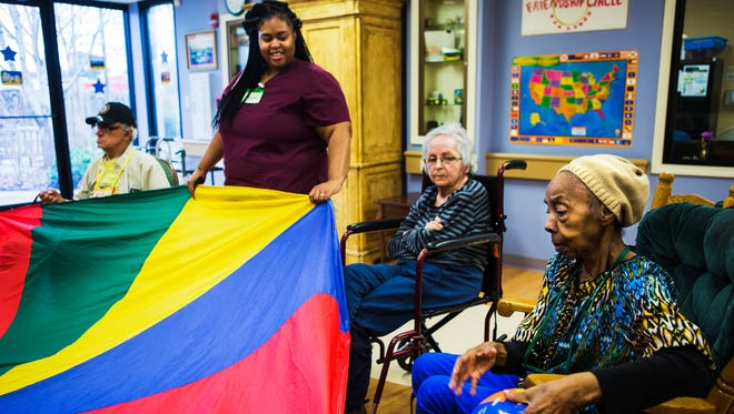"""January 17, 2017 - George Hawthrone (from left), personal care attendant or """"best friend"""" Brittney Hunter, Mary Owens and Rachel Adams play the exercise game """"Parachute"""" at Dorothy's Place on Tuesday. The nonprofit Alzheimer's & Dementia Services of Memphis Inc. plans to open a third day-center across from Crosstown Concourse."""