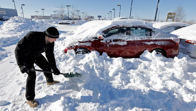 A salesman digs out cars covered in snow at a dealership in Indianapolis Jan. 7. Indianapolis is on track for its snowiest single month on record.