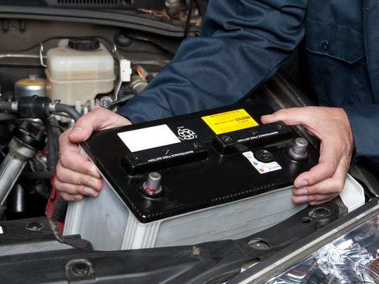 A car mechanic replaces a battery.