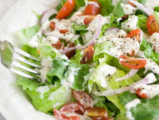 A house salad with leafy greens, grape tomatoes, red