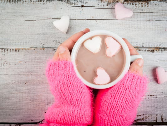 Girl drinking hot chocolate with marshmallows's hearts