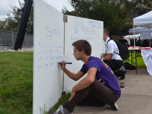 Collin McAliley, a senior business economics and finance major, writes a quote on the free speech wall.