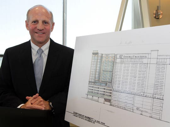 El Paso attorney Jim Scherr stands next to the artist rendering of the hotel that he and the Marriott Hotel chain are building Downtown next to the DoubleTree Hotel, which he owns.