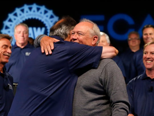 Fiat Chrysler Automobiles CEO Sergio Marchionne, left, and United Auto Workers President Dennis Williams hug during a ceremony to mark the opening of contract negotiations Tuesday, July 14, 2015 in Detroit. The union's contracts with GM, Ford and Fiat Chrysler expire Sept. 14. (AP Photo/Paul Sancya)