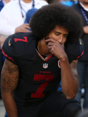 Colin Kaepernick, seen here last year with the San Francisco 49ers, kneels during the national anthem before a game vs. Arizona.