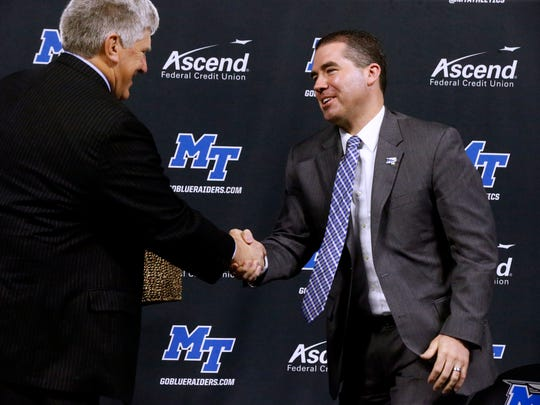 MTSU Athletic Director Chris Massaro presents the new MTSU Mens Coach Nick McDevitt a gift during a press conference at Murphy Center, on Tuesday March 27, 2018.